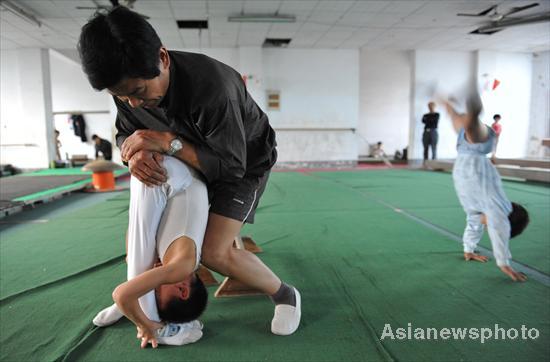 трененер растягивает мальчика